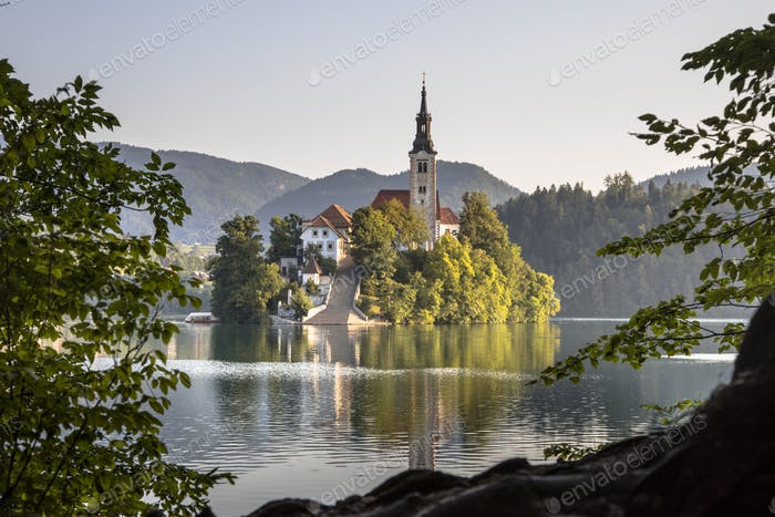 Island in lake Bled in hazy morning light seen through foliage
