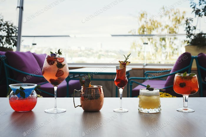 Variety of alcohol cocktails on gray table