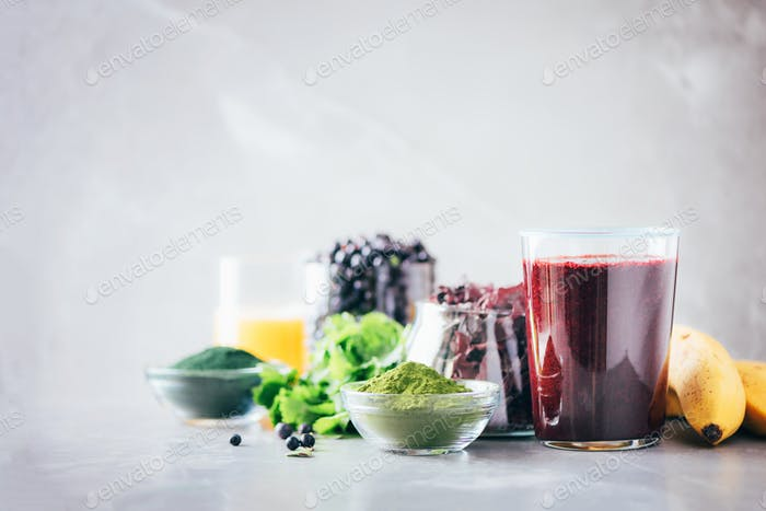 Healthy eating, alkaline diet, vegan concept. Blueberries, bilberry, barley grass juice, spirulina