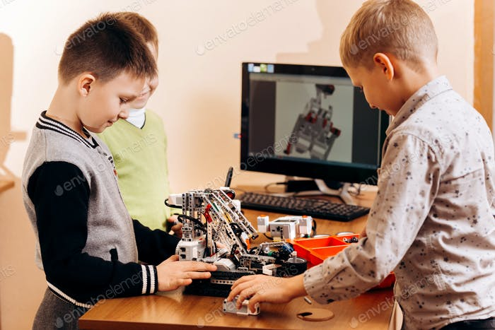 Three smart boys are making robots from the robotic constructor at the desk with computer in the