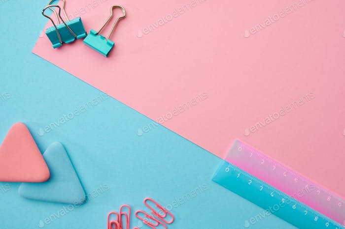 Paper clips, ruler, blue and pink background