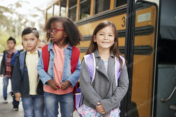 Young girl at the head of the queue for the school bus