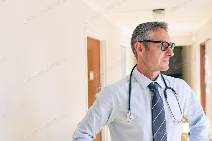 Side view of matured Caucasian male  doctor standing in corridor at retirement home