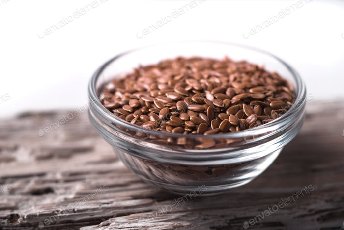 Linen seeds in a glass bowl on wooden table