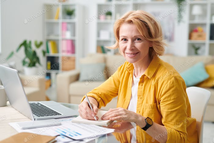 Smiling mature female in casualwear holding pen over paper while making notes