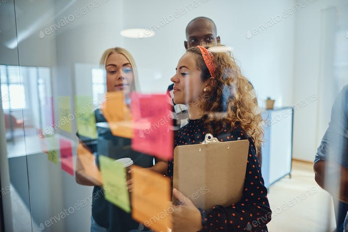 Diverse team of designers brainstorming together with sticky notes