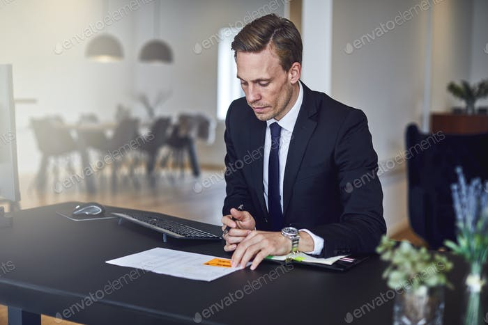 Businessman reading through paperwork at his desk in an office