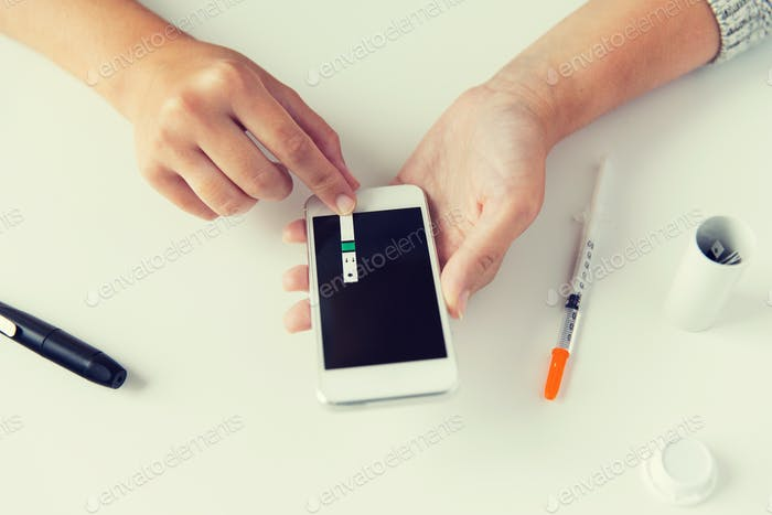 close up of woman with smartphone doing blood test