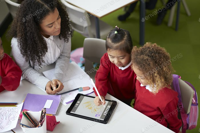 Elevated view of two girls using a tablet computer sitting at table in an infant school class