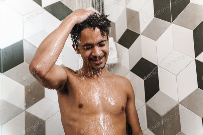 Photo of half-naked african american man smiling while taking shower