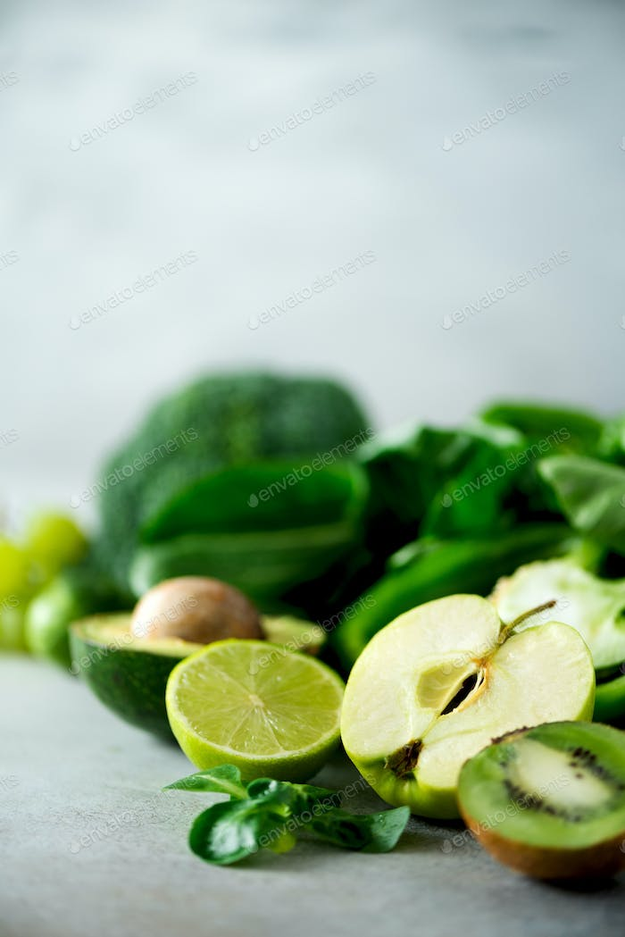 Organic green vegetables and fruits on grey background. Copy space. Green apple, lettuce, cucumber