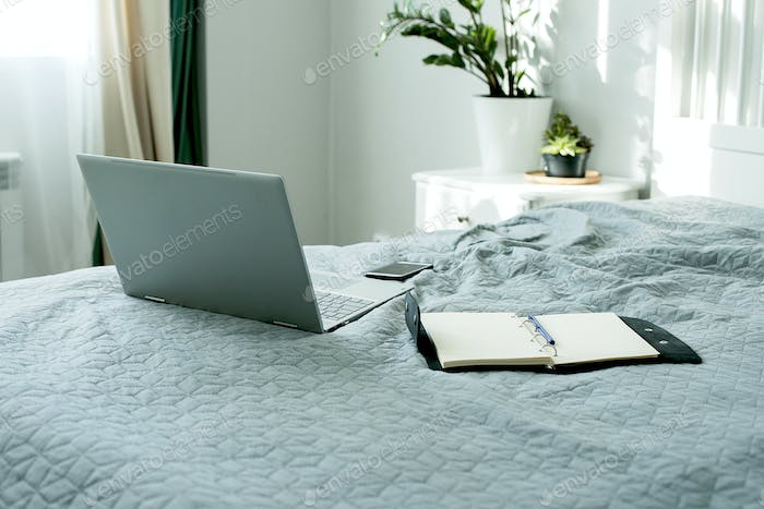 Laptop, mobile and open notebook on bed. Concept of female business, home education, shopping online