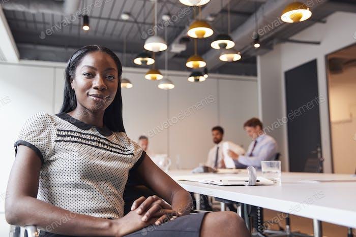 Портрет деловой женщины в современном зале заседаний с коллегами в фоновом режиме