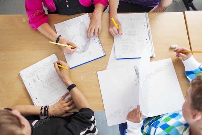 Hochwinkelansicht von Junior-Hochschülern, die am Schreibtisch im Klassenzimmer studieren