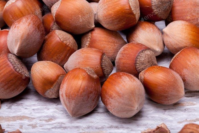 Brown Hazelnuts on white wooden background