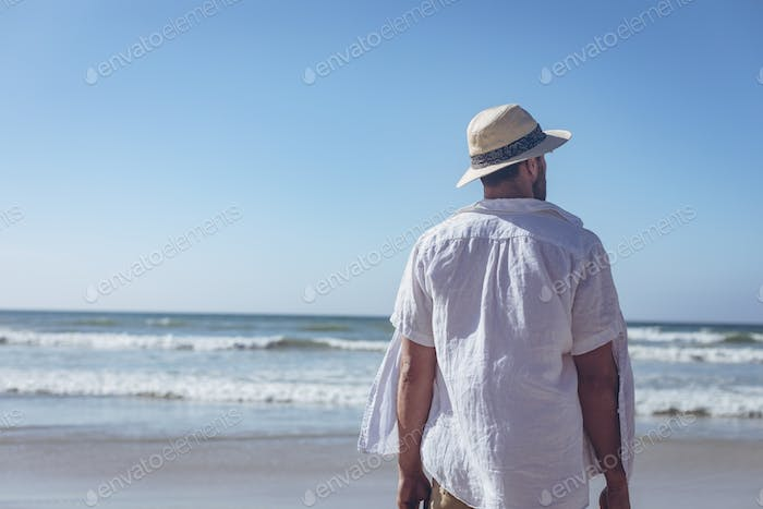 Rear view of young Caucasian man standing at beach on sunny day. He wears a hat