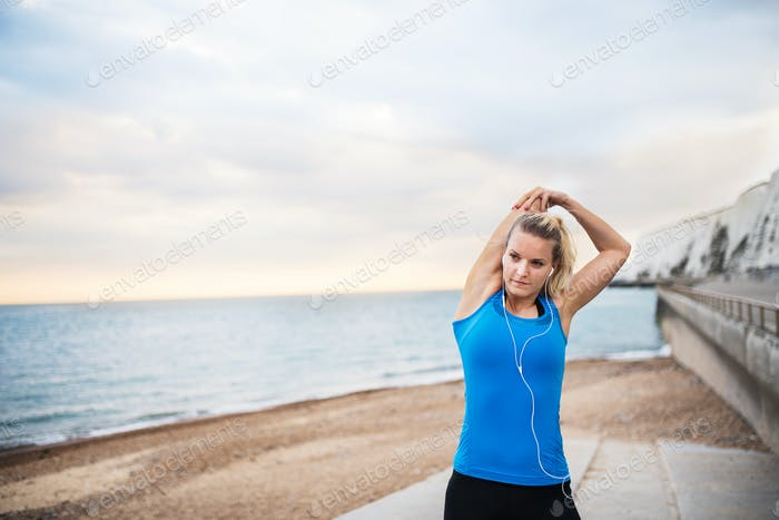 Young sporty woman runner with earphones standing on the beach outside, stretching.