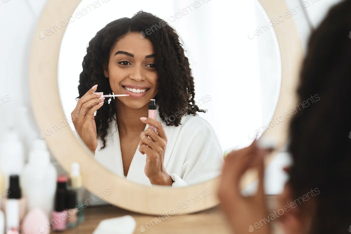 Makeup Routine. Smiling African American Girl Applying Lip Gloss Near Mirror