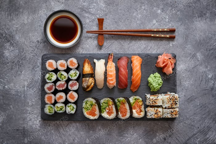 Composition of different kinds of sushi rolls placed on black stone board