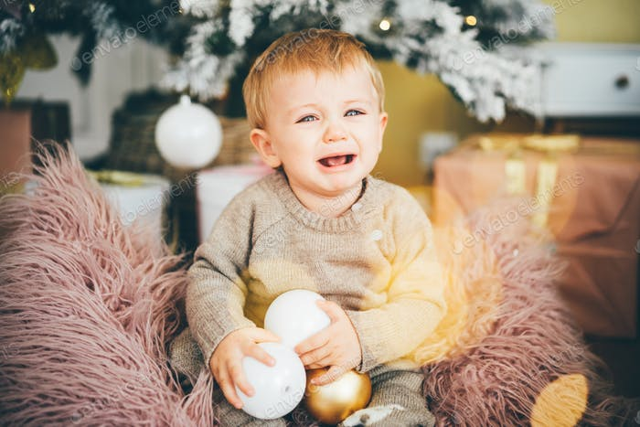 Cute crying baby sitting near Xmas tree at home.