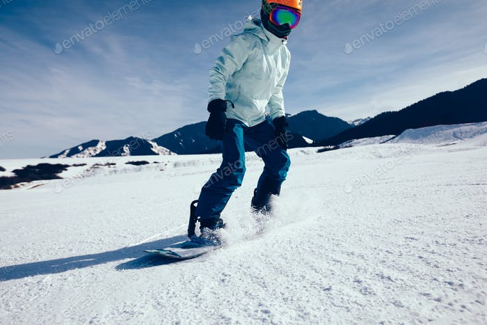 woman snowboarder descent on winter mountain slope