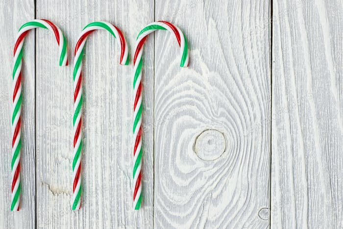 Christmas cane decoration on wooden background