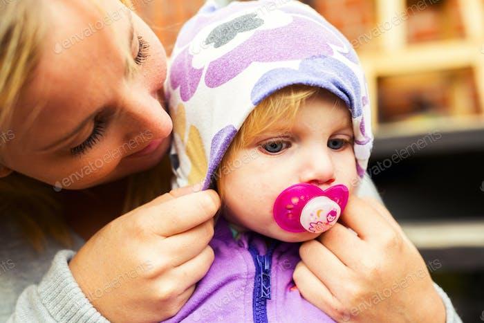 Mutter Anpassung Kapuze auf dem Kopf des Babys