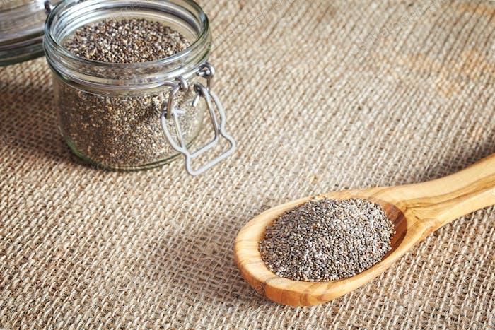 Chia-Samen in einem Holzlöffel und Glas.