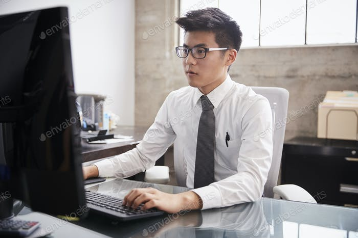 Young Asian businessman using a computer at an office desk