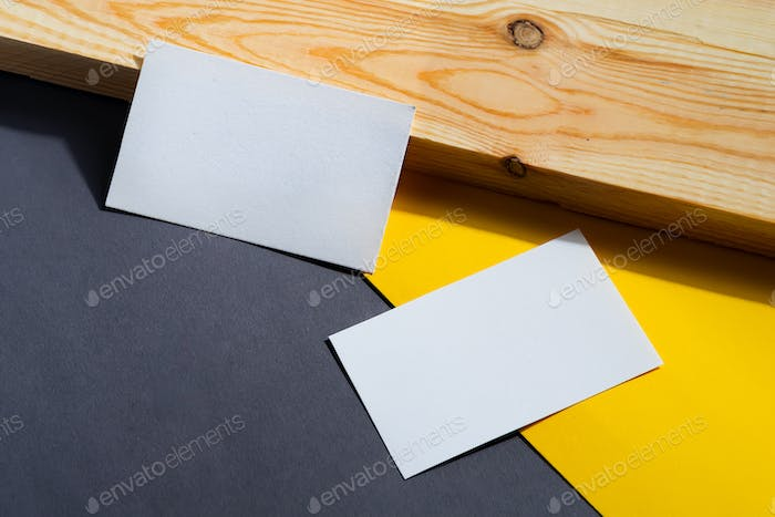 Business card with place for text. Background from yellow and gray paper lying diagonally.
