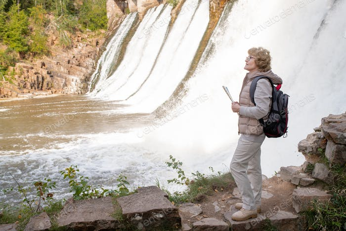 Mature female hiker with backpack and map guide standing by waterfalls