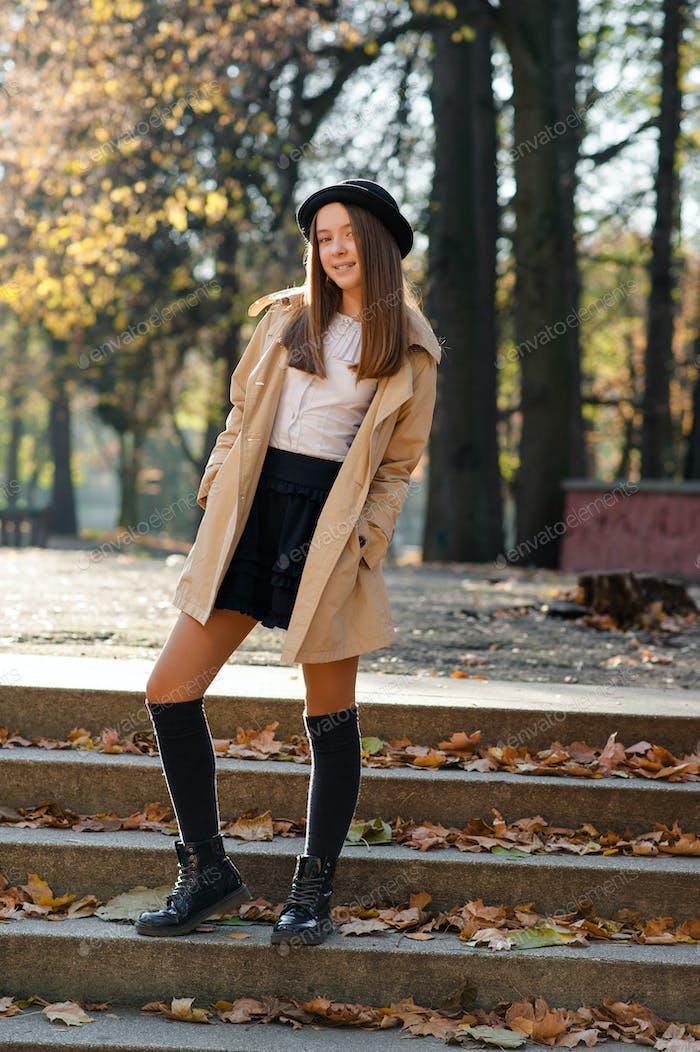 Schöne Teenager-Mädchen auf den Stufen in einem Herbstpark