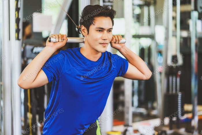 Young Asian man wearing sportswear doing excecise with the bar in gym fitness sport complex