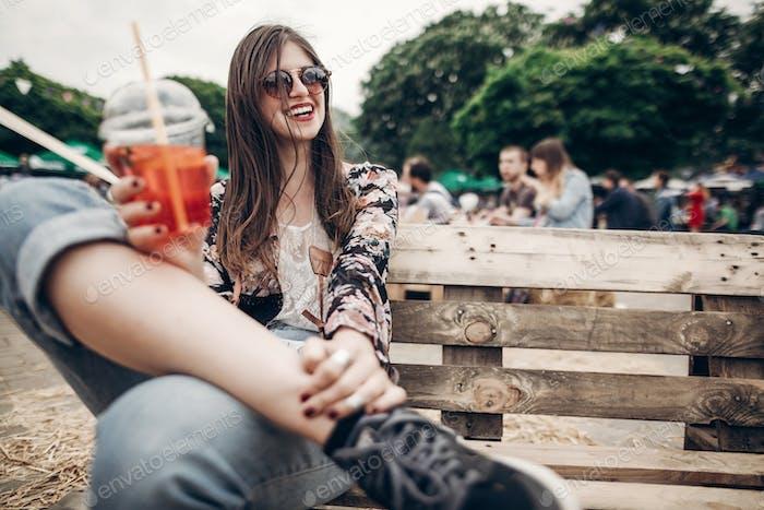 Cooles Boho Mädchen in Denim und Bohemian Kleidung, mit Cocktail und Kamera