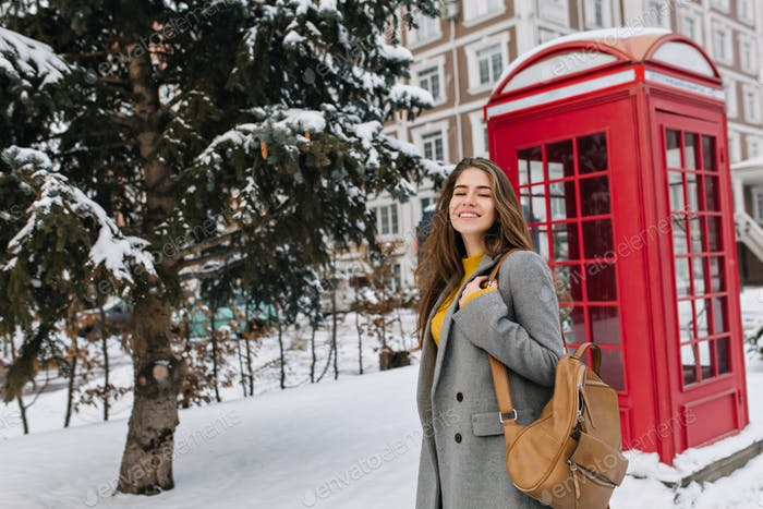 Romantic young woman wears gray coat walking down the street with phone booth on background. Outdoor