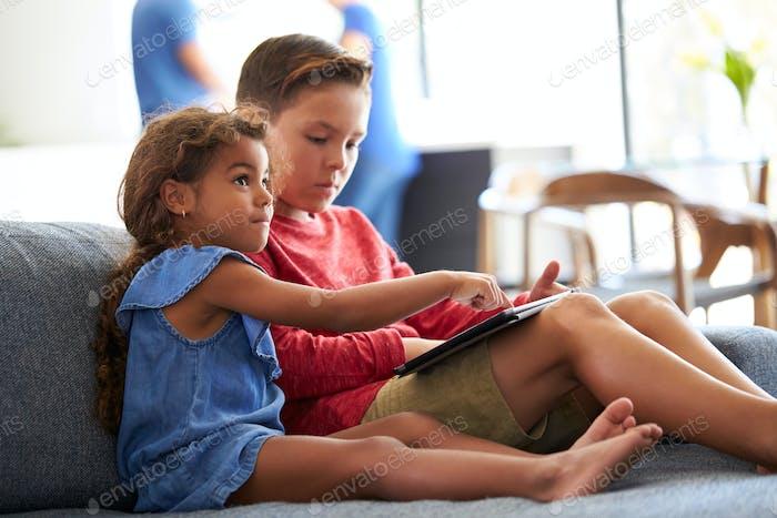 Junge und Mädchen Spielen Video spiele auf Digital-Tablet Während Familientreffen zu Hause