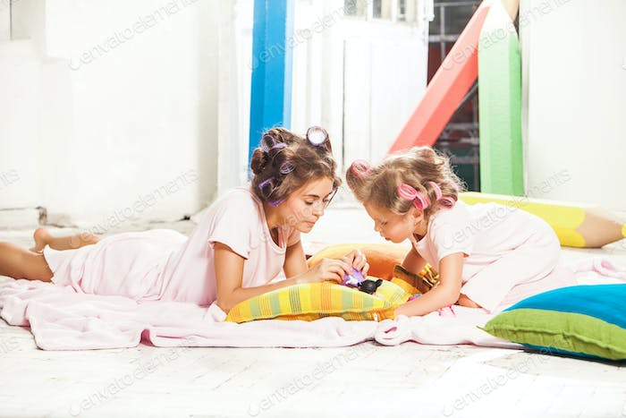 Little girl sitting with her mother and playing