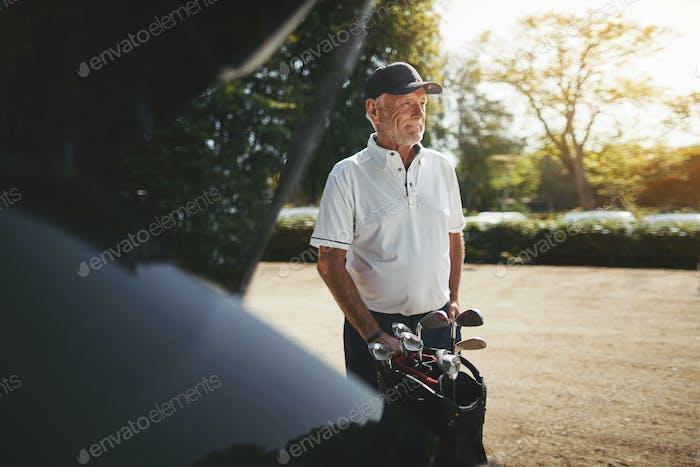 Senior man putting his golf clubs in a car trunk