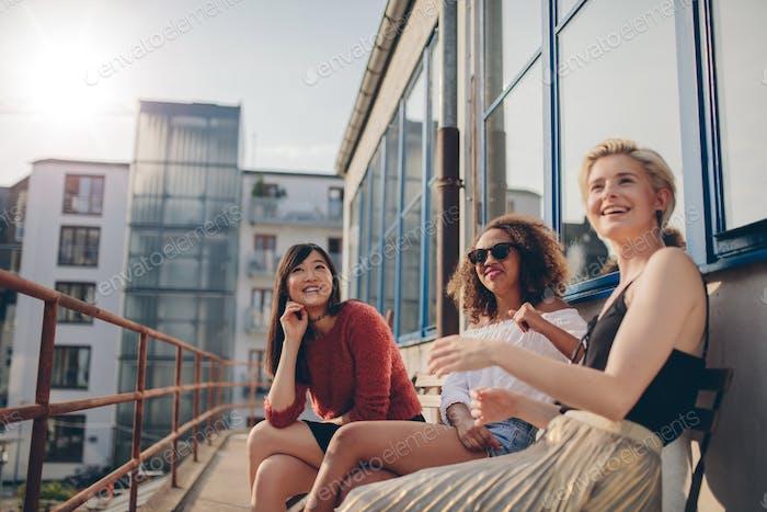 Lächelnde Frauen entspannen im Freien auf der Terrasse