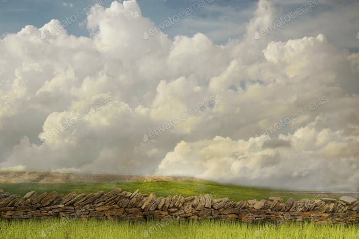 55214,Stone wall and grassy fields under clouds in rural landscape