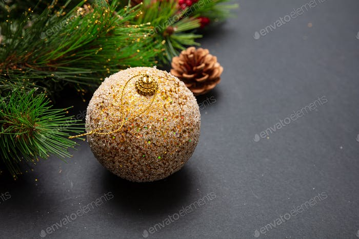 Xmas bauble shiny gold color against grey black background, high angle