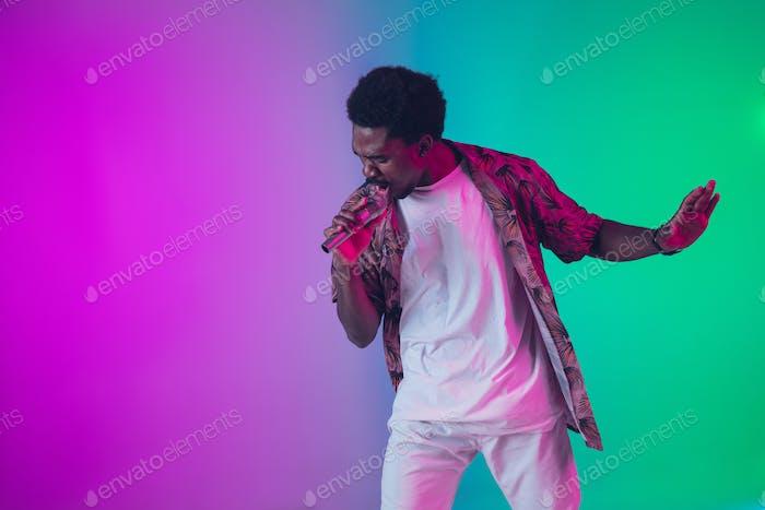 Afroamerikanischer männlicher Sänger Porträt isoliert auf Farbverlauf Studiohintergrund in Neonlicht