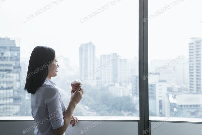 Smiling young businesswoman holding a coffee cup and looking out the window