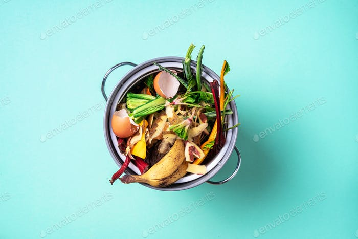 Top view of kitchen food waste collected in recycling compost pot. Peeled vegetables on chopping