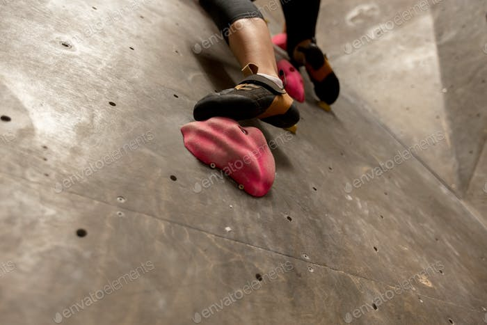 foot of woman exercising at indoor climbing gym