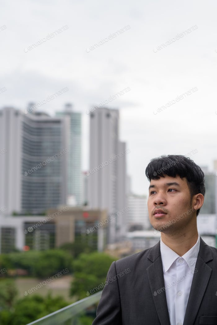 Portrait of young Asian businessman against view of the city