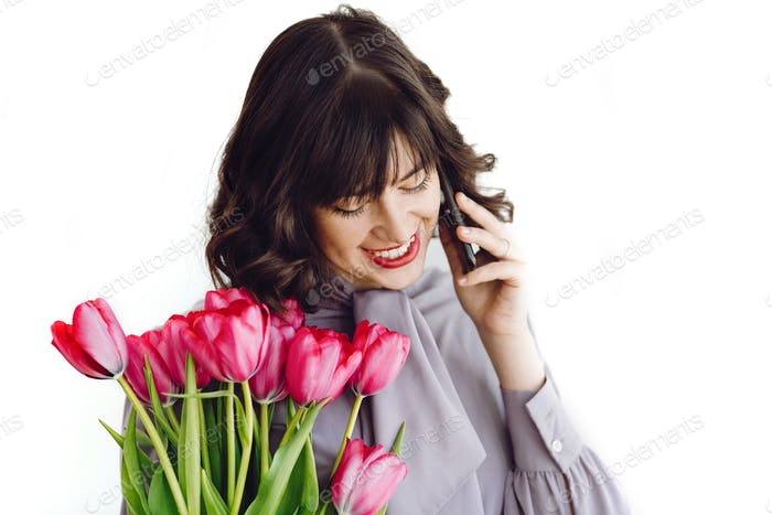 Beautiful happy girl  talking on phone and smiling, holding red tulips