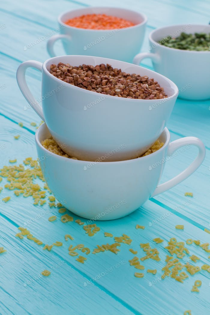 Cups with dry buckwheat and other cereals.
