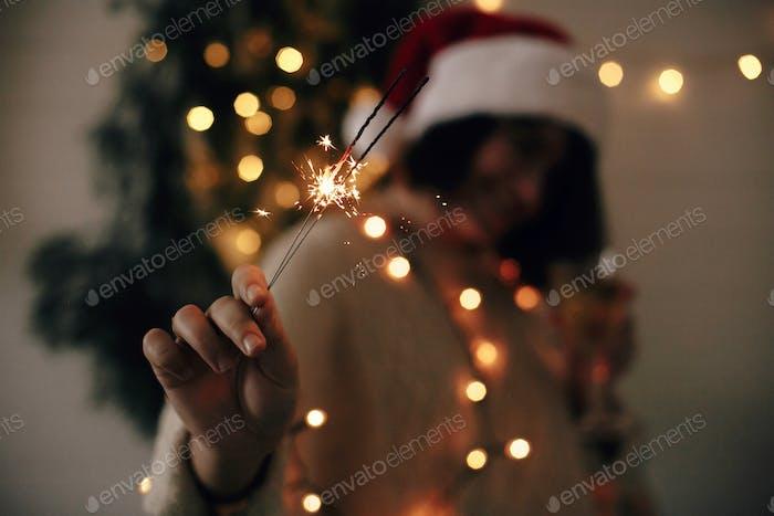 Big sparkler burning in hand of stylish girl in santa hat