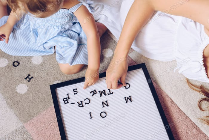 Pregnant mother and her daughter playing with a letter board